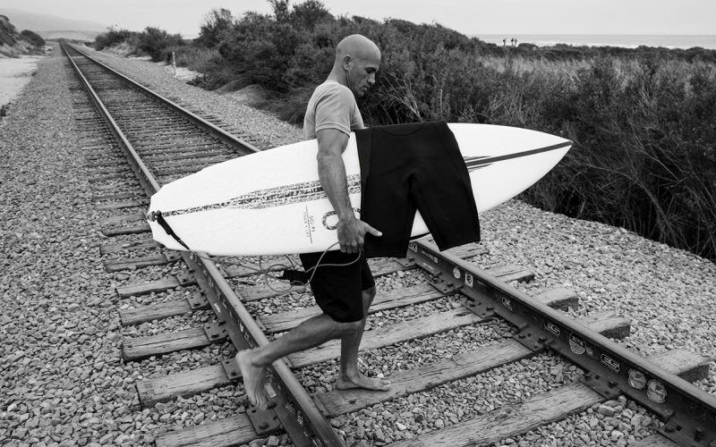 surfer crossing railway