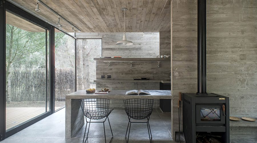 h3 house by luciano kruk modern architecture Argentina kitchen with chairs and wood burner - Concrete Cabin H3 House south east of Buenos Aries in Mar Azul