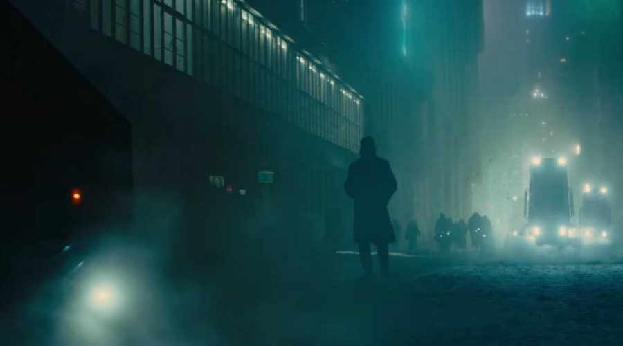blade runner 2049 film photo with Ryan Gosling Blade Runner actor in a long coat and boots in blue street lights