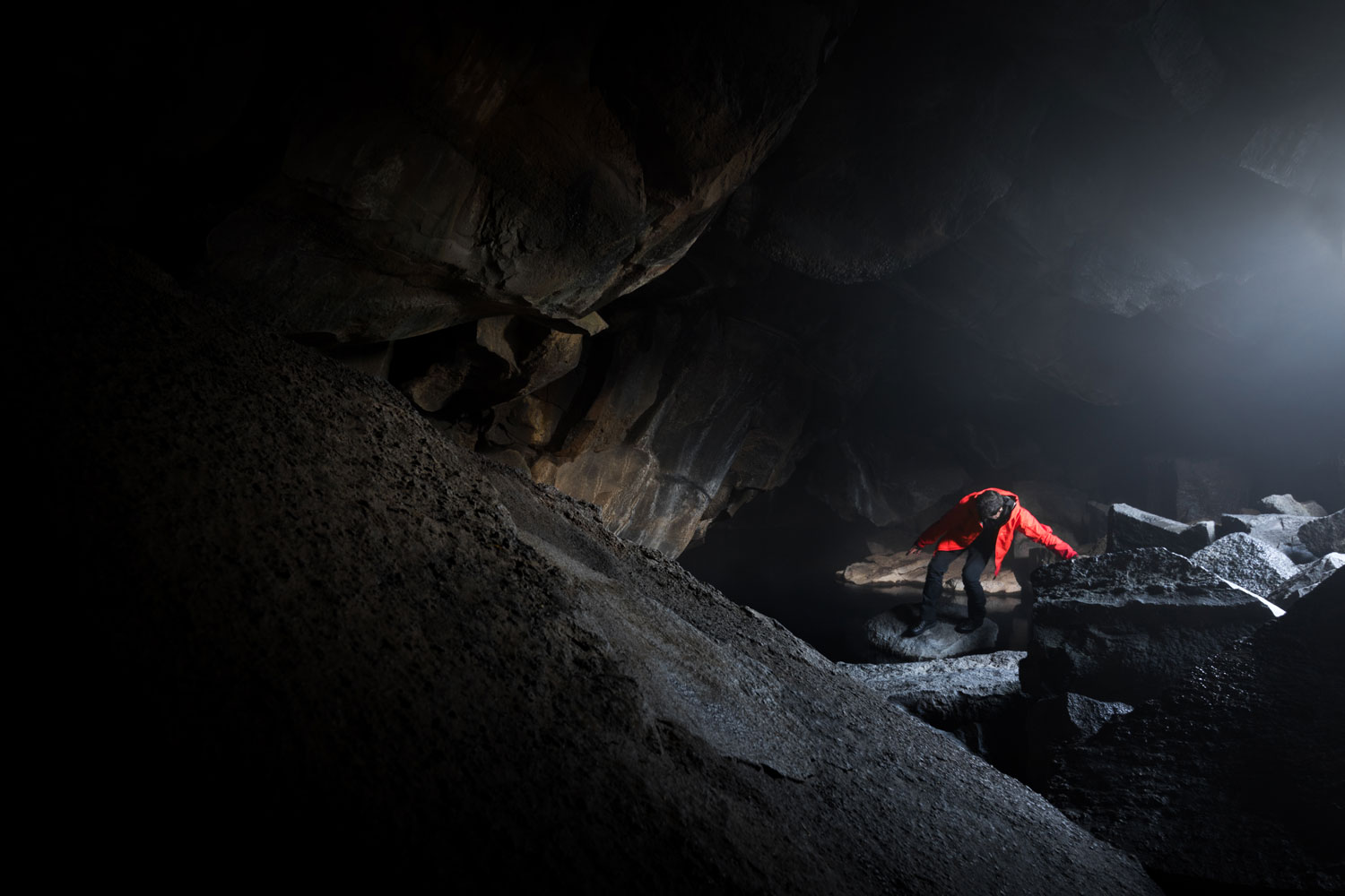GRJOTAGJA CAVE in iceland with a figure wearing a red Arcteryx beta sv jacket