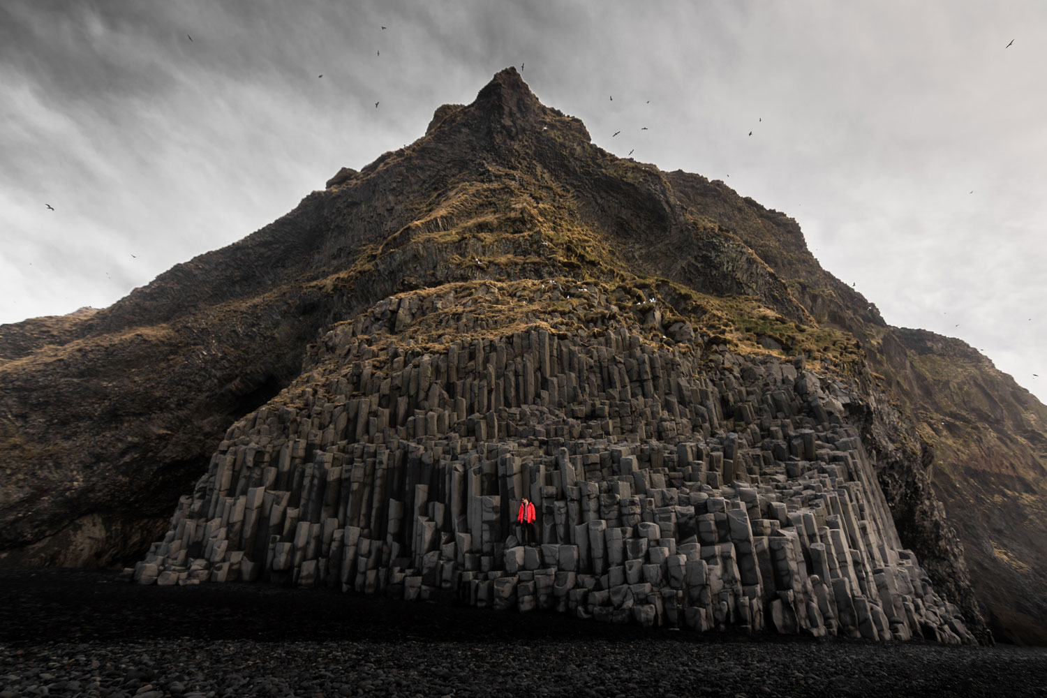 REYNISFJARA BEACH in iceland with a figure wearing a red Arcteryx beta sv jacket