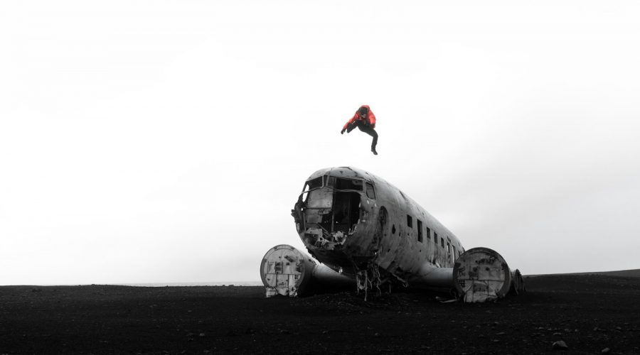United States Navy Douglas Super DC-3 airplane wreckage on Solheimasandur 's black sand beach in iceland with figure jumping wearing a red Arc'teryx Beta SV Jacket
