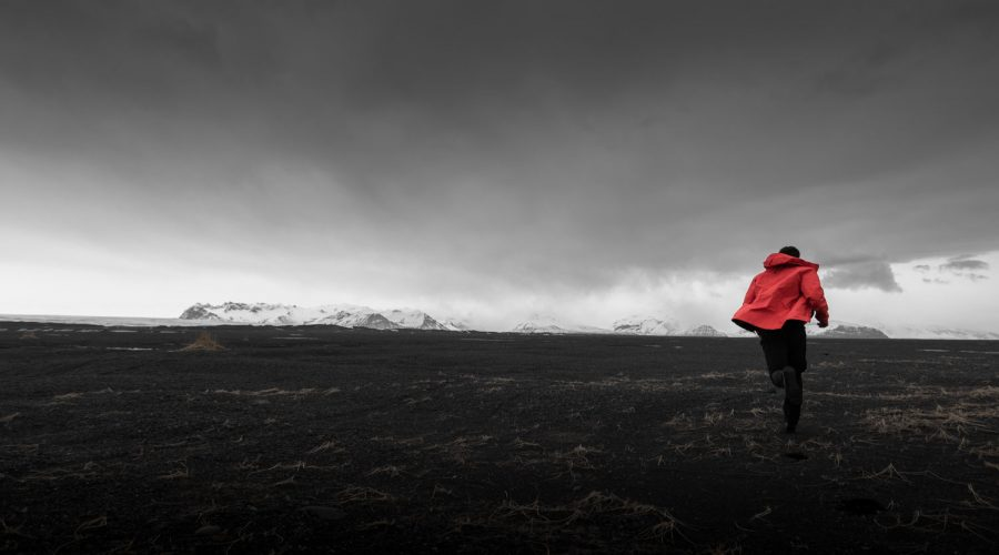 Solheimasandur 's black sand beach in iceland with figure running wearing a red Arc'teryx Beta SV Jacket